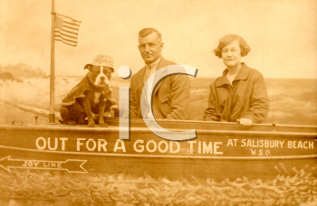 Royalty Free Photo of a Couple and Dog in a Boat