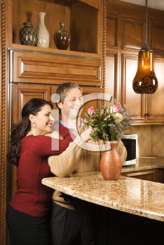 Royalty Free Photo of a Woman Leaning on a Man While He Arranges Flowers in a Vase in the Kitchen