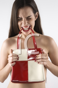 Royalty Free Photo of a Topless Woman Holding a Purse to Her Chest and Biting the Handles