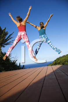 Royalty Free Photo of Women Jumping into the Air With Arms and Legs Outstretched