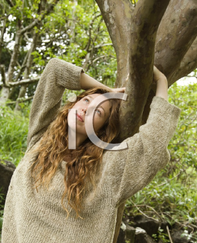 Royalty Free Photo of a Woman Smiling Holding on a Tree in the Forest
