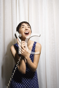 Royalty Free Photo of a Pretty Young Woman Holding a Telephone Receiver to Her Ear and Laughing
