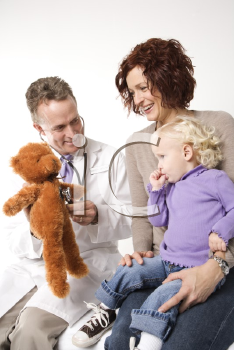 Royalty Free Photo of a Doctor Holding a Stethoscope to a Teddy Bear While a Mother and Daughter Watch