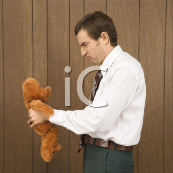 Royalty Free Photo of a Man Holding a Stuffed Animal and Looking Upset