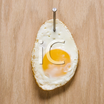 Royalty Free Photo of a Fried Egg Bailed to Wood