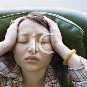 Royalty Free Photo of a Woman Sitting in a Green Chair With Eyes Closed and Hands on Her Head