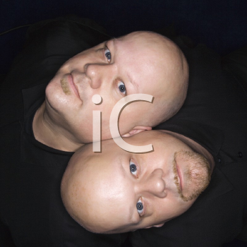 Royalty Free Photo of an Aeriel View of Identical Twin Men Sitting Back to Back and Looking Up