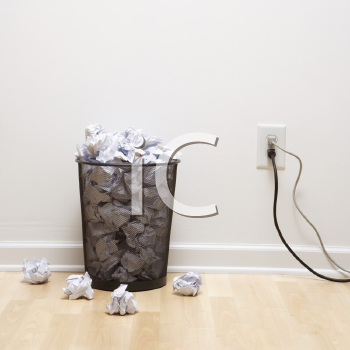 Royalty Free Photo of a Full Wire Mesh Trash Can With Crumpled Paper Next to an Electrical Outlet and Plugs