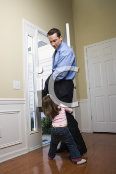 Royalty Free Photo of a Businessman at an Opened Door With His Daughter Tugging on His Leg