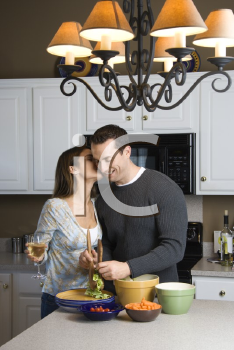 Royalty Free Photo of a Woman Kissing a Man at the Kitchen Counter