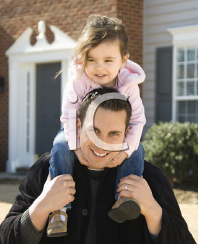 Royalty Free Photo of a Father Carrying His Daughter on His Shoulders