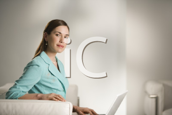 Royalty Free Photo of a Professional Businesswoman Sitting in an Office Working on a Laptop Computer