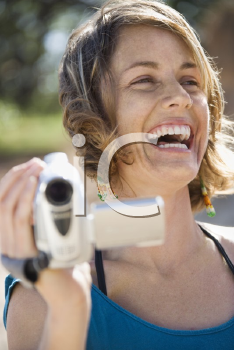 Royalty Free Photo of a Woman Outdoors Holding a Video Camera Laughing