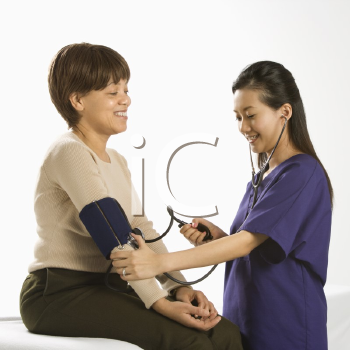 Royalty Free Photo of a Female Medical Practitioner Checking Blood Pressure of a Female Patient