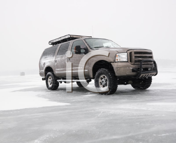 Royalty Free Photo of a Four Wheel Drive Truck With All Terrain Tires and Roof Rack Parked on Desolate Frozen Lake in Green Lake, Minnesota, USA