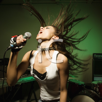 Royalty Free Photo of a Female Swinging Her Head and Hair While Singing Into a Microphone
