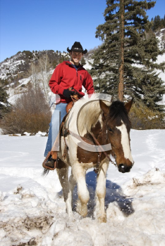 Royalty Free Photo of a Man Horseback Riding in the Snowy Mountains