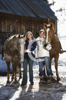 Royalty Free Photo of Two Women Standing With Horses