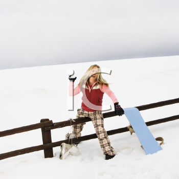 Royalty Free Photo of a Young Woman in Winter Clothes by a Fence in a Snowy Field Smiling While Getting Ready to Throw a Snowball