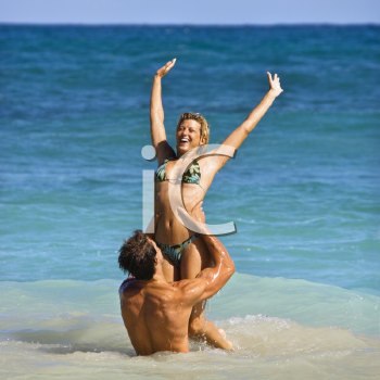 Royalty Free Photo of a Man Holding a Woman Up Out of Water on Maui, Hawaii Beach
