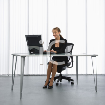 Royalty Free Photo of a Businesswoman Sitting at a Desk With Her Computer Working