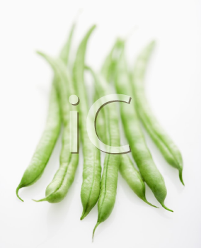 Selective focus shot of green beans on white background.
