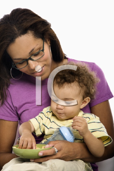 Royalty Free Photo of a Mom Sitting With Toddler Son on Her Lap Eating Cereal