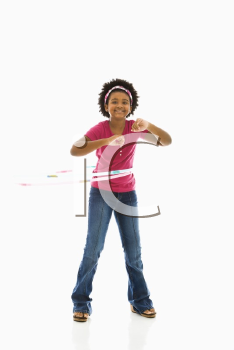 African American girl playing with hula hoop and smiling at viewer.