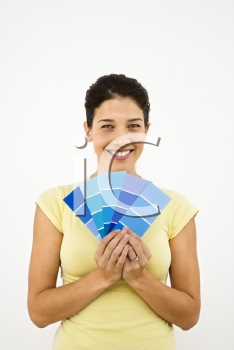 Royalty Free Photo of a Pretty Smiling Woman Holding Paint Sample Cards in Front of a White Wall