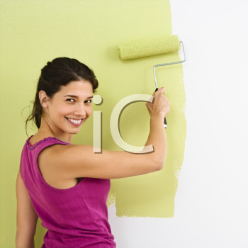 Royalty Free Photo of a Woman Painting the Interior Wall of Home with a Paint Roller