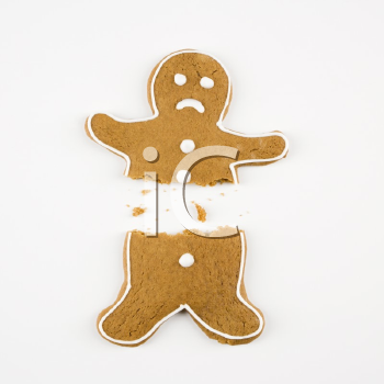 Royalty Free Photo of a Frowning Gingerbread Cookie Broken in Half