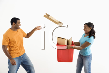 Royalty Free Photo of a Woman  Holding a Recycling Bin While a Man Tosses Cardboard Into It