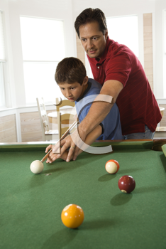 Man shooting game of pool with young boy.  Vertically framed shot.