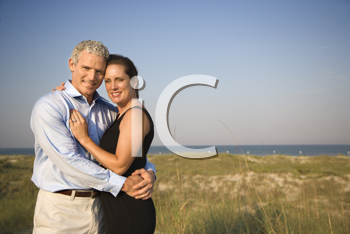 Attractive causcasian couple embrace and smile at the camera. Horizontal shot.