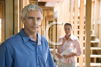 Serious looking couple stand inside their home construction site. Horizontal shot.