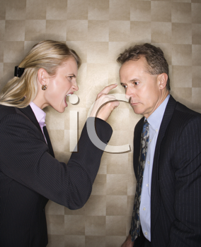 Caucasian mid-adult businesswoman yelling and pointing at middle-aged businessman. Vertical format.