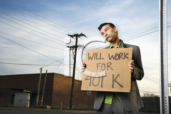 Young businessman stands on a street corner holding a sign that reads 'will work for 401 K'. Horizontal shot.