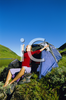 Royalty Free Photo of a Woman Yawning Outside a Tent