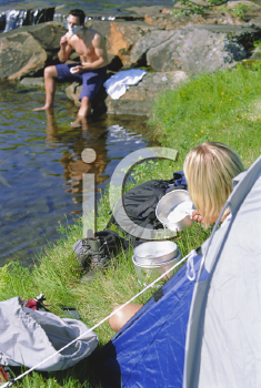 Royalty Free Photo of a Couple Camping and the Man is Shaving