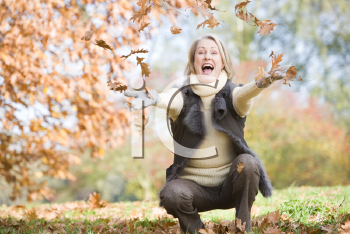 Royalty Free Photo of a Woman Throwing Leaves