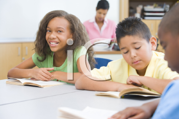 Royalty Free Photo of Students Reading in a Classroom With the Teacher in the Background