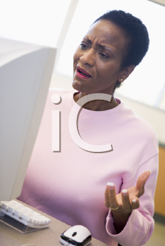Royalty Free Photo of a Woman Looking Frustrated at a Computer