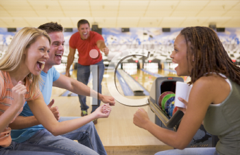 Royalty Free Photo of a Man Bowling With Friends