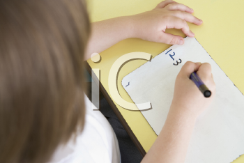 Royalty Free Photo of a Student Writing Numbers in Class