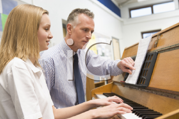 Royalty Free Photo of a Girl With the Teacher at the Piano