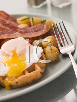Royalty Free Photo of Waffles with Bacon, Fried Potatoes and a Broken Fried Egg