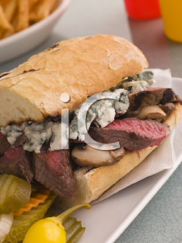 Royalty Free Photo of a Steak and Roquefort Sandwich with Fries, Gherkins and Chilies