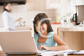 Royalty Free Photo of a Girl at a Laptop in the Kitchen