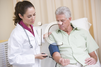 Royalty Free Photo of a Doctor Checking a Man's Blood Pressure