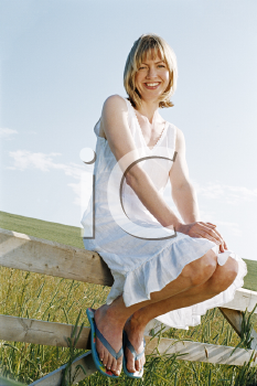 Royalty Free Photo of a Woman Sitting on a a Fence